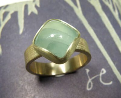 Verlovingsring 'Linnen'. Geelgouden linnenstructuur met kussen geslepen aquamarijn. Engagement ring 'Linnen'. Yellow golden ring with linnen structure and aquamarine. Oogst goudsmeden Amsterdam.
