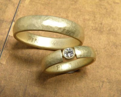 Trouwringen 'ritme'. Geelgouden ring met kussen hamerslag en diamant. Geelgouden ring met kussen hamerslag. Wedding rings 'Rhythm'. Yellow golden ring with hammering and a diamond. Yellow golden ring with hammering. Oogst goudsmeden Amsterdam.