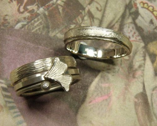 Partnerringen 'Verzameling' en 'Erosie'. Witgouden aanschuifringen met spitse hamerslag, ginkgo blaadje, bol en diamant. Witgouden ring met gelaagde structuur. Wedding rings 'Collection' & 'Erosion'. White golden stack rings with hammering, ginkgo leaf, sphere and diamond. White golden ring with layered structure. Oogst Amsterdam.
