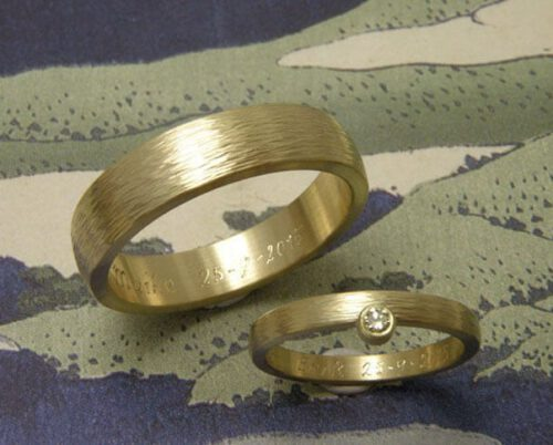 Trouwringen 'ritme'. Geelgouden ring met hamerslag en diamant. Geelgouden ring met hamerslag. Wedding rings 'Rhythm'. Yellow golden ring with hammering and diamond. Yellow golden ring with hammering. Uit het Oogst atelier Amsterdam.