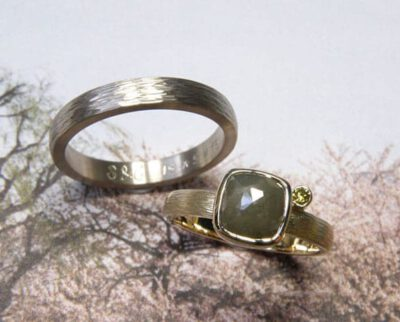 Trouwringen Ritme. Van eigen oud goud vervaardigde ring met hamerslag en een olijf en groene diamant. Witgouden ring met hamerslag. Wedding rings 'Rhythm'with hammering. Made from own heirloom gold and a green and olive diamond for her. White gold for him. Oogst ontwerp & creatie