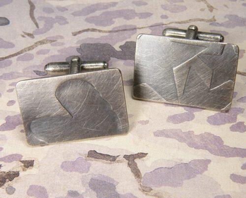 Zilver geoxideerde manchetknopen met verdiept motief van 3 sterren en 1 hart. Silver cufflinks with 3 stars and 1 heart. Oogst goudsmeden Amsterdam.