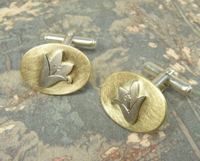 Manchetknopen 'In bloei' Geelgouden ovaaltje met witgouden campanula klokjes. Vervaardigd van eigen goud. Maatwerk uit het Oogst atelier Amsterdam. Cufflinks with a flower motive, created from heirloom gold. Design by Oogst.