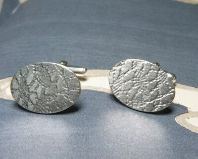 Zilveren ovale manchetknopen met kant afdruk. Silver oval shaped cufflinks with lace texture. Oogst goudsmeden Amsterdam.