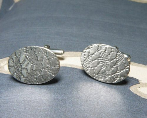 Zilveren ovale manchetknopen met kant afdruk. Silver oval shaped cufflinks with lace texture. Oogst goudsmeden Amsterdam.