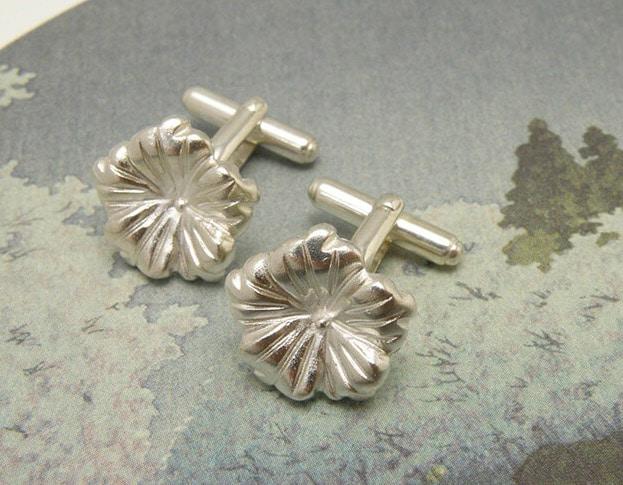 Zilveren manchetkopen met strakke bloemen. Silver cufflinks with flowers. Uit het Oogst atelier Amsterdam.