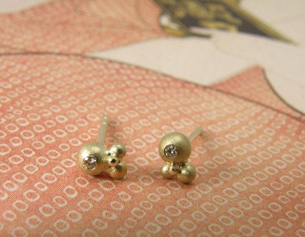 Geelgouden besjes oorstekers met diamant.