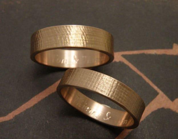 Roodgouden trouwringen met linnen structuur, brede vlakke ringen