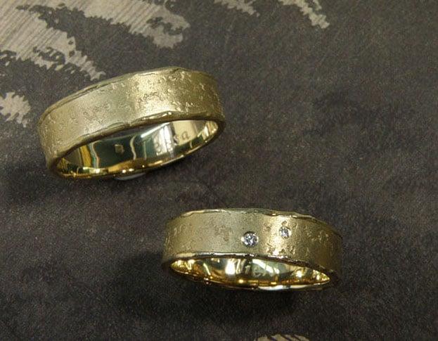 Trouwringen met organische structuur. Geelgouden erosie ringen met diamant.