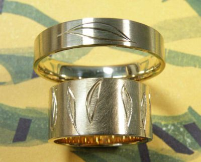 Handgegraveerde trouwringen 'Lineair'. Geelgouden brede ring met rondom bladeren. Geelgouden ring met een blad. Hand engraved wedding rings 'Lineair'. Yellow golden wider ring with leaves all around. Yellow golden ring with leafs. Oogst goudsmeden Amsterdam.