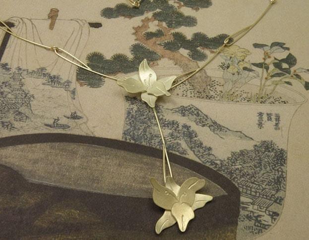 Geelgouden lelies bungelend aan elegante handgemaakte draadschakels. Yellow golden necklace with lillies and handmade chain. Oogst Amsterdam.