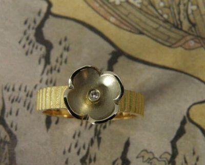 geelgouden ring 'In bloei' met witgouden lotusbloem en diamant. Yellow golden ring 'In bloom' with white golden lotus flower and diamond. Uit het Oogst atelier Amsterdam.