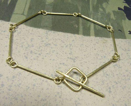 Roodgouden rinkelband met spitse hamerslag. Rose golden hammered bangle. Oogst goudsmeden Amsterdam.
