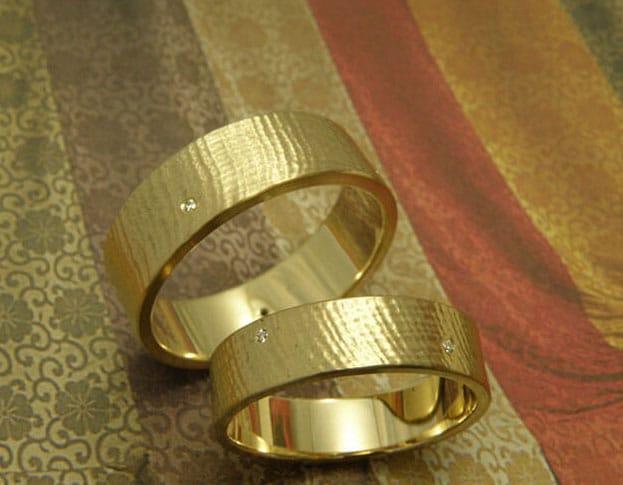 Geelgouden trouwringen met linnen structuur.