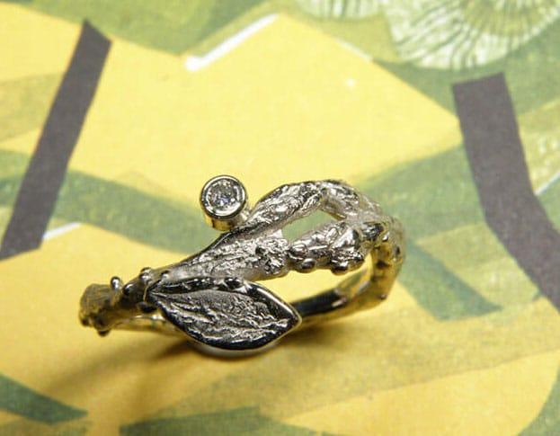 Witgouden 'Boomgaard' ring. Speels takje met blaadje en diamant. Oogst goudsmeden Amsterdam
