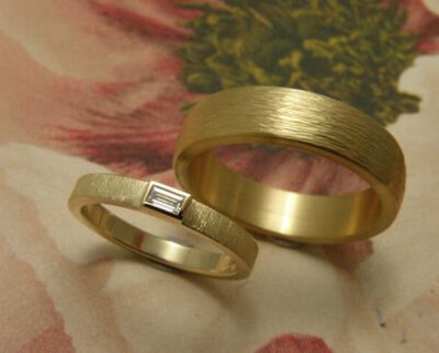 Trouwringen 'Eenvoud' & 'Ritme'. Geelgouden ring met diamant en geelgouden ring met hamerslag. Wedding Rings 'Simplicity' & 'Rhythm'. Yellow golden ring with diamond and yellow golden ring with hammering. Uit het Oogst atelier Amsterdam.