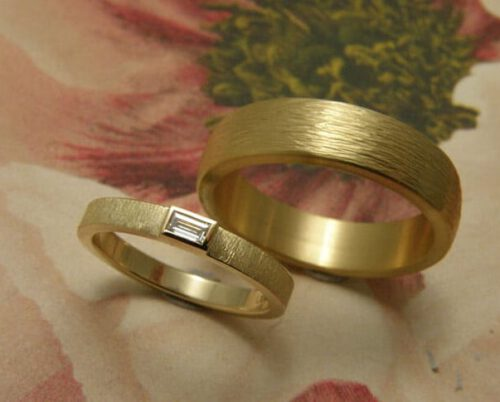 Trouwringen 'Eenvoud' & 'Ritme'. Geelgouden ring met diamant en geelgouden ring met hamerslag. Wedding Rings 'Simplicity' & 'Rhythm'. Yellow golden ring with diamond and yellow golden ring with hammering. Uit het Oogst atelier Amsterdam.
