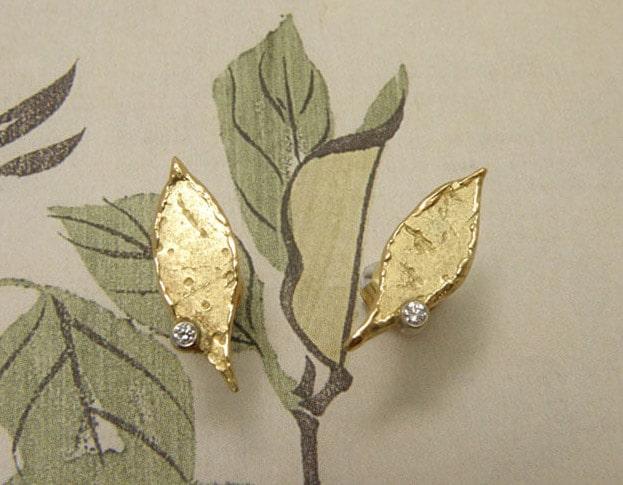 Geelgouden blaadjes oorstekers met 2 diamanten. Yellow golden leaf earstuds with 2 diamonds. Uit het Oogst atelier Amsterdam.