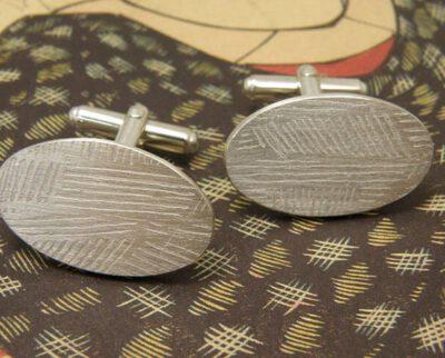 Zilveren ovale manchetknopen met strepen patroon. Silver oval cufflinks with stripes pattern. Oogst goudsmeden Amsterdam.