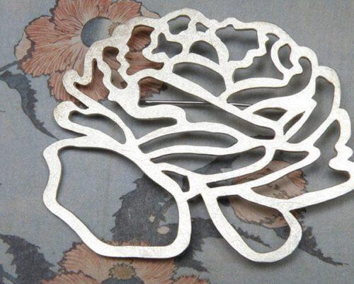 'In bloei' speld met zilveren ranonkel. 'In bloom' pin with silver flower. Uit het Oogst atelier Amsterdam.
