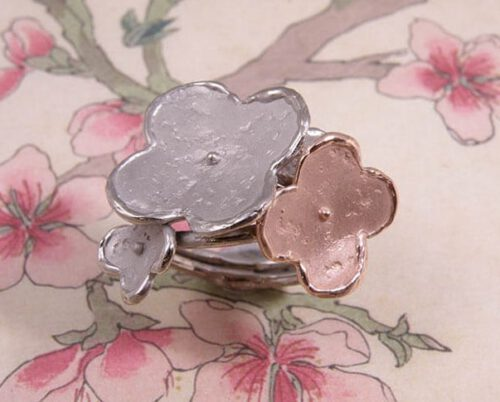 Ring In Bloei, witgoud en roodgouden bloemen. Ring In Bloom, white gold and rose gold flowers. Uit het Oogst goudsmid atelier. Made in the Oogst goldsmith studio.