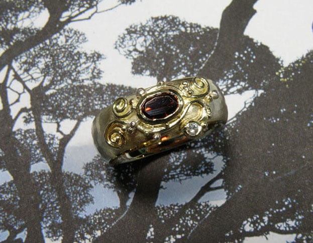 Ring van oud goud gemaakt met filigrain krullen motief en eigen granaat en diamant. Ring made from own heirloom gold with a curly filigrain motive and a garnet and diamond. Oogst goudsmid Amsterdam.