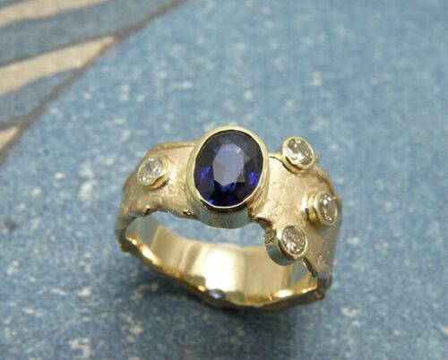 Ring 'Erosie' verlopende ring met structuur vervaardigd van eigen geelgoud met eigen diamanten en saffier uit een dierbare, maar versleten, ring. Ring 'Erosion' ring with structure made of heirloom yellow gold, diamonds and sapphire from a beloved, but worn out, ring. Uit het Oogst atelier Amsterdam.