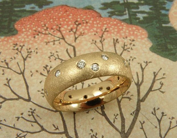 Ring 'Eenvoud' bolle ring van eigen roségoud vervaardigd met eigen diamanten speels rondom erin gezet. Ring 'Simplicity' ring made of heirloom rose gold with playfully placed heirloom diamonds. Oogst goudsmeden Amsterdam.