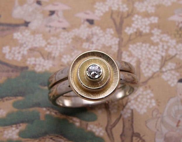Ring Cirkels, witgoud met geelgouden kommetjes en diamant. Ring Circles, white gold with yellow gold bowls and diamond. Uite het Oogst goudsmid atelier. Made in the Oogst goldsmith studio.