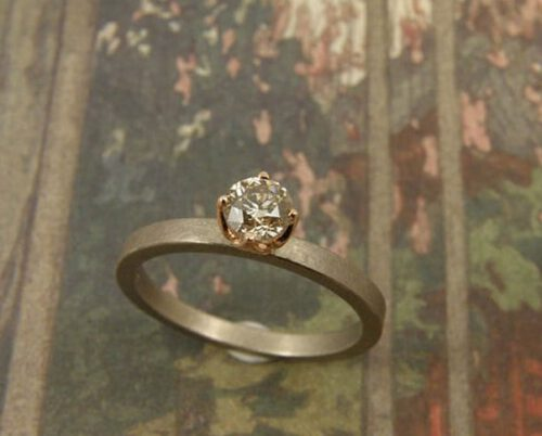 Witgouden ring met diamant in roodgoud zetting. White golden ring with a diamond. Oogst goudsmeden Amsterdam.
