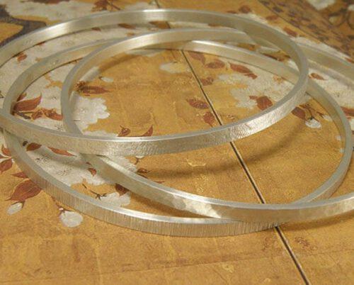 Zilveren rinkelbanden, ieder met een andere structuur. Silver bangles with different structures. Uit het Oogst atelier Amsterdam.