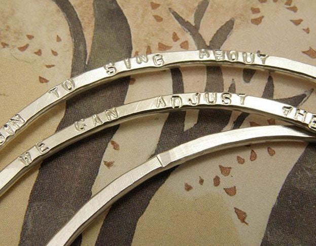 Rinkelbanden zilver met gestempelde tekst. Silver banges with stamped texts. Uit het Oogst goudsmid atelier. Made in the Oogst goldsmith studio.