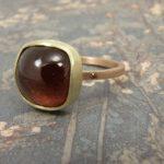 Roodgouden ring met donkerroze toermalijn in geelgouden zetting. Rose golden ring with pink tourmaline. Uit het Oogst atelier Amsterdam.