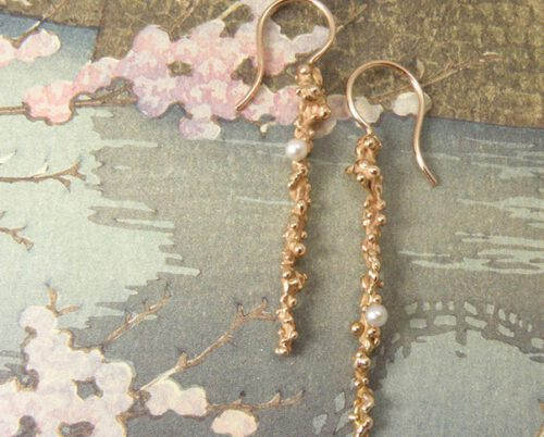 Roodgouden bolletjes met krul en grijze zoetwaterparels. Earrings with rose golden spheres and grey pearls. Uit het Oogst atelier Amsterdam.