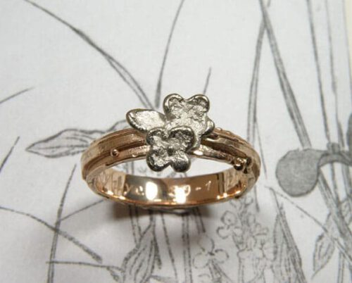 Roodgouden structuur ring met witgouden bloemen. Rose gold textured ring with white gold flowers. Uit het Oogst goudsmid atelier. Made in the Oogst goldsmith studio.