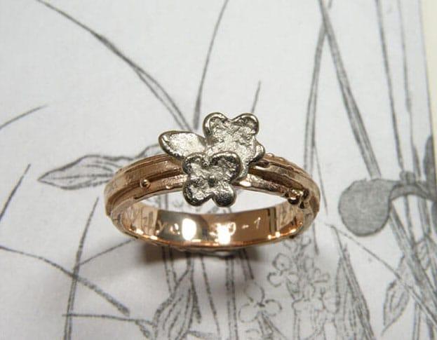 Roodgouden structuur ring met witgouden bloemen. Rose gold textured ring with white gold flowers. Uit het Oogst goudsmid atelier. Made in the Oogst goldsmith studio.