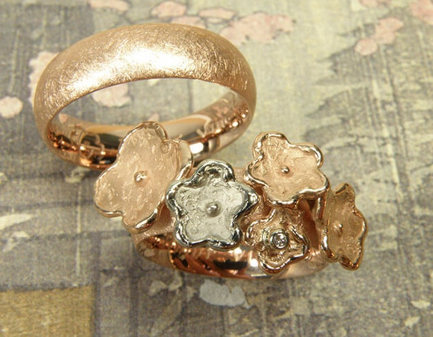 Trouwringen 'In bloei' en 'Eenvoud'. Roodgouden ring met bloemen, waarvan 1 witgoud en een diamant. Roodgouden ring. Wedding rings 'In bloom' & 'Simplicity'. Rose golden ring with flowers, one of which in white gold, and a diamond. Rose golden ring. Oogst goudsmeden Amsterdam.
