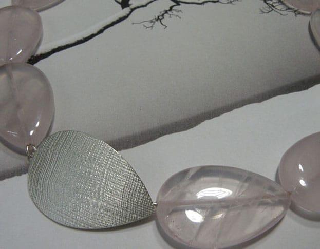 Druppelvorm geslepen rozenkwarts met zilveren sluiting en linnen structuur. Drop shape rose quartz necklace with silver clasp and linnen structure. Oogst Amsterdam.