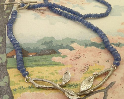 Blog over saffier. Saffier collier met witgouden blaadjes en takjes. Sapphire necklace with white old twigs and leafs. Oogst goudsmid Amsterdam.