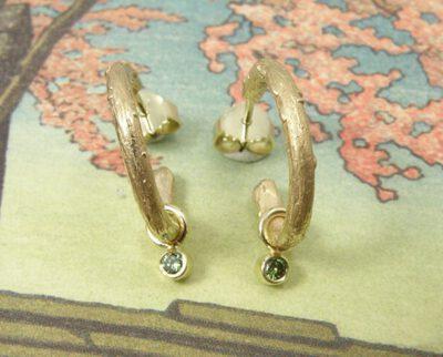 Oorsieraden 'Boomgaard' takjes creolen van eigen goud vervaardigd met 2x 0,05 crt diamant fancy green. Earrings 'Orchard' twig earrings made of heirloom gold with 2x 0,05 crt diamond fancy green. Uit het Oogst atelier Amsterdam.