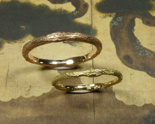 Trouwringen 'Boomgaard'. Geelgouden fijne takjesring en roodgouden takjesring. Wedding rings 'Orchard'. Delicate yellow golden twigring and rose golden twigring. Oogst goudsmeden Amsterdam.