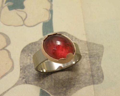 Witgouden ring met rode toermalijn in roodgouden wolk zetting. Oogst goudsmeden Amsterdam.
