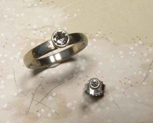 Trouwring'Ritme' witgoud met fijne hamerslag en eigen diamant. Oorsieraad 'Boleet' witgoud met eigen diamant. Wedding ring 'Rhythm' whitegold with hammering and own diamond. Earring 'Boletus' white gold with own diamond. Oogst goldsmith Amsterdam