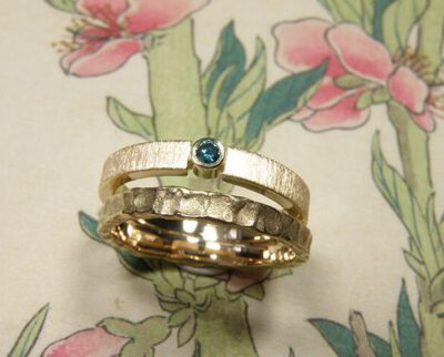Trouwring Deining en Eenvoud. Aanschuifringen met structuur en ocean blue diamant. Van eigen goud vervaardigd. Wedding rings Swell and Simplicity. Stack rings. made from heirloom gold. With ocean blue diamond. Oogst goldsmith Amsterdam. Edelsmid.