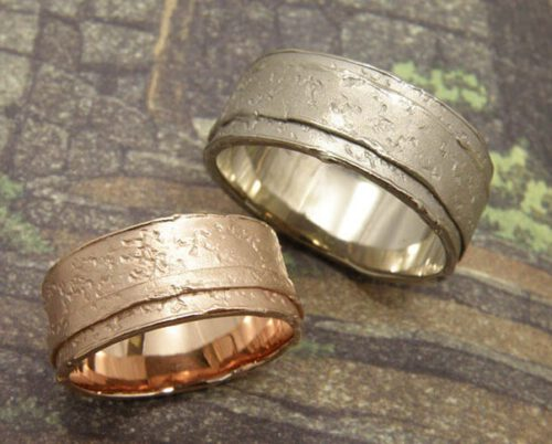 Trouwringen 'Erosie'. Roodgouden brede structuur ring met smalle laag. Witgouden brede structuur ring met brede laag. Wedding rings 'Erosion'. Rose golden structure ring with small layer. White golden structure ring with small layer. Oogst goudsmeden Amsterdam.