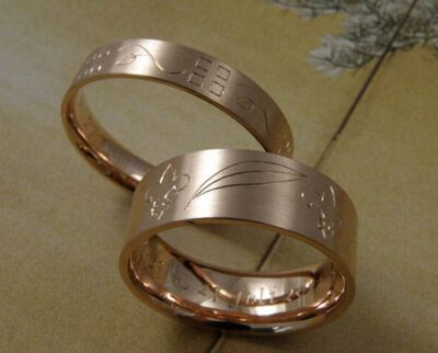 Trouwringen 'Lineair'. Roodgouden ring met handgravure art deco en roodgouden ring met handgravure franse lelie en palmbladeren. Wedding rings 'lineair'. Rose golden ring with art deco hand engraving and rose golden ring with french lillies and palm leafs hand engraving. Oogst goudsmeden Amsterdam.