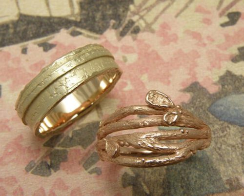 Partnerringen 'Boomgaard' en 'Erosie'. Roodgouden twijgjes ring met blaadjes en geelgouden gelaagde structuur ring. Wedding bands 'Orchard' & 'Erosion'. Rose golden twig ring with leafs and a yellow golden ring layered ring with structure. Oogst goudsmeden Amsterdam.