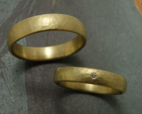 met hammerslag, waarvan 1 met diamant. Yellow golden hammered 'Rhythm' wedding rings, ow which 1 with diamond. Uit het Oogst atelier Amsterdam.