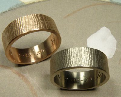 Trouwringen 'Linnen'. Witgouden brede linnenstructuur en roodgouden brede linnenstructuur. Wedding rings 'Linnen'. White golden wider ring with linnen structure and rose golden wider ring with linnen structure. Oogst goudsmeden Amsterdam.