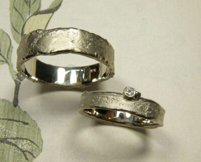 Trouwringen 'Erosie'. Witgouden structuur ring met een diamant en witgouden brede structuur ring. Wedding rings 'Erosion'. White golden structure ring with a diamond and a wider white golden ring with structure. Oogst Amsterdam.
